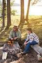 Senior couple near a lake sitting by a camp fire Royalty Free Stock Photo
