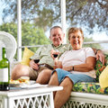 Senior couple outside on patio looking at camera photo of happy holding wine glasses Royalty Free Stock Photos