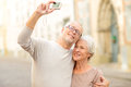 Senior couple photographing on city street Royalty Free Stock Photo