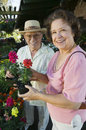 Senior couple at the plant nursery portrait of a happy shopping for flowers Royalty Free Stock Photos