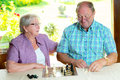 Senior couple playing chess older women and men at home Royalty Free Stock Photos