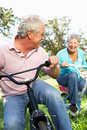 Senior couple playing on children's bikes Royalty Free Stock Photos