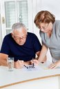 Senior couple playing leisure games concentrated at home Royalty Free Stock Images