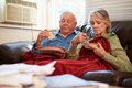 Senior couple with poor diet keeping warm under blanket depressed looking unhappy Stock Images