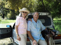 Senior couple posing beside car boot man holding golf bag smiling portrait men Royalty Free Stock Photos