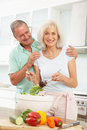 Senior Couple Preparing Salad In Modern Kitchen Royalty Free Stock Photo