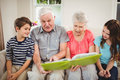 Senior couple reading a book with their grand children and in living room Stock Image