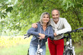 Senior couple ready for riding bicycle cheerful with in country path Stock Photos