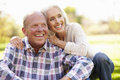 Senior couple relaxing in autumn landscape smiling Royalty Free Stock Photos
