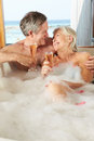 Senior couple relaxing in bath drinking champagne together smiling to each other Stock Image