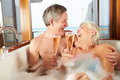 Senior couple relaxing in bath drinking champagne together smiling to each other Stock Images