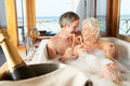 Senior couple relaxing in bath drinking champagne together smiling to each other Royalty Free Stock Photos