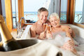 Senior couple relaxing in bath drinking champagne together smiling to each other Royalty Free Stock Photo