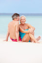 Senior couple relaxing on beautiful beach together smiling Stock Photography