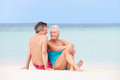 Senior couple relaxing on beautiful beach together smiling Stock Photos