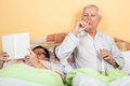 Senior couple relaxing in bed retired with alcohol and book Stock Photos