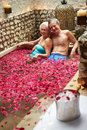 Senior couple relaxing in flower petal covered pool at spa smiling to camera Royalty Free Stock Image