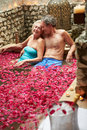 Senior couple relaxing in flower petal covered pool at spa smiling to camera Stock Image