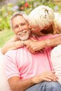 Senior Couple Relaxing In Garden Royalty Free Stock Photos