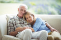 Senior couple relaxing on sofa in living room Royalty Free Stock Photo