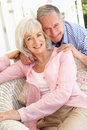Senior Couple Relaxing Together On Sofa Royalty Free Stock Images