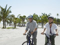 Senior couple riding bicycles on beach happy tropical Royalty Free Stock Images