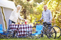 Senior couple riding bikes on camping holiday in countryside Stock Photo