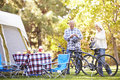 Senior couple riding bikes on camping holiday in countryside smiling Stock Image