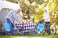 Senior couple riding bikes on camping holiday in countryside smiling Stock Photo