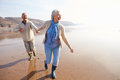 Senior Couple Running Along Winter Beach Royalty Free Stock Photo