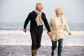 Senior Couple Running Along Winter Beach Royalty Free Stock Photo