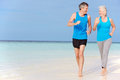 Senior couple running beautiful beach smiling Royalty Free Stock Image