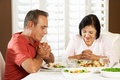 Senior Couple Saying Grace Before Meal At Home Stock Photography