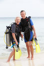 Senior couple with scuba diving equipment enjoying holiday smiling to camera Stock Photo