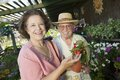 Senior couple shopping for flowers at plant nursery portrait Royalty Free Stock Photo