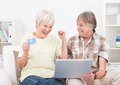 Senior couple shopping online happy using laptop with credit card Stock Photos