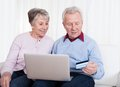 Senior couple shopping online sitting on couch and with laptop computer Stock Images