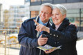 Senior couple on sightseeing tour happy doing city trip with a map Stock Photos