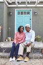 Senior couple sit on steps outside their house, vertical
