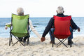 Senior Couple Sitting On Beach In Deckchairs Royalty Free Stock Photo