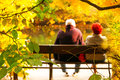 Senior couple sitting on bench in autumn park Royalty Free Stock Images