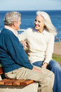 Senior Couple Sitting On Bench By Sea Together Stock Image