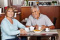 Senior couple sitting at breakfast in hotel happy a Royalty Free Stock Photo