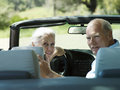 Senior couple sitting in convertible car looking over shoulder smiling rear view portrait Stock Photography