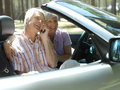 Senior couple sitting in convertible car using mobile phone smiling side view Royalty Free Stock Photos