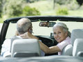 Senior couple sitting in convertible car woman looking over shoulder smiling rear view portrait women Royalty Free Stock Photography