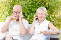 Senior couple sitting on a couch drinking alcohol glass of they phone Stock Image