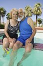 Senior couple sitting on edge of swimming pool portrait Stock Images