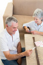 Senior couple sitting on floor playing cards at home in living room Stock Image