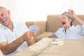 Senior couple sitting on floor playing cards at home in living room Stock Photo